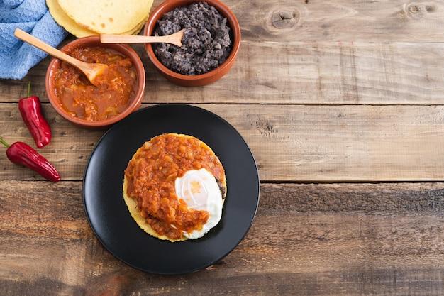 Plat huevos rancheros, petit-déjeuner mexicain sur socle en bois. cuisine mexicaine. copiez l'espace.