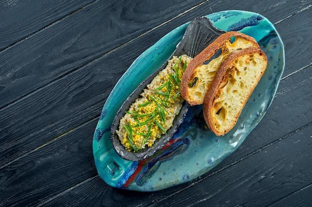 Un plat israélien classique est le hareng forshmak dans une assiette bleue, servi avec des croûtons sur une surface en bois sombre. vue rapprochée sur vorschmack ou forshmak