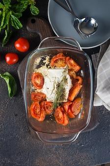 Plat italien de pâtes mélangées avec du fromage feta cuit au four et des tomates sur fond sombre. fetapasta. recette virale tendance, mise à plat, espace de copie