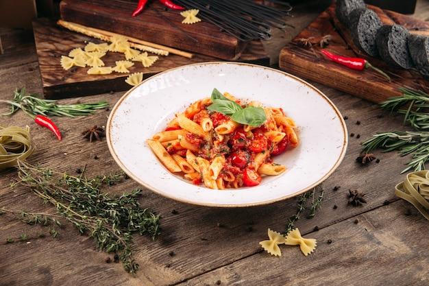 Plat italien de pâtes penne arabiatta en sauce piquante sur la table en bois