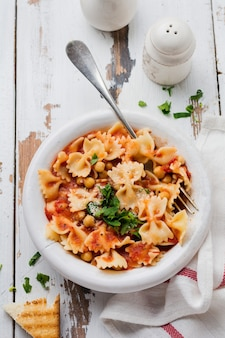 Plat italien traditionnel, chaudrée, potage, pâtes et ceci servi dans une vieille assiette sur fond de bois ancien. style rustique. vue de dessus.