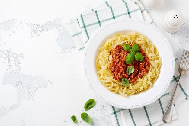 Plat italien traditionnel de pâtes fettuccine avec sauce bolognaise, basilic et parmesan dans une assiette blanche sur fond de bois clair. vue de dessus.