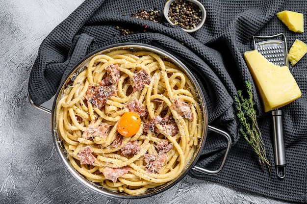 Plat italien traditionnel spaghetti carbonara au bacon dans une sauce à la crème dans une poêle. fond gris. vue de dessus