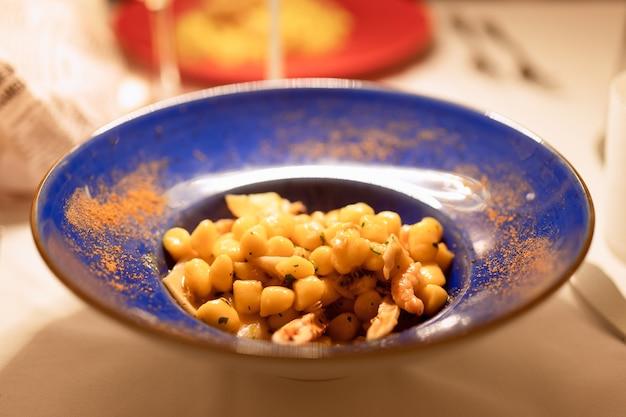 Plat italien typique gnocchi aux fruits de mer dans un bol bleu