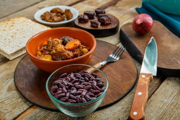 Plat juif chelnt avec de la viande dans une assiette sur une table en bois sur un support à côté d'un couteau et d'ingrédients.