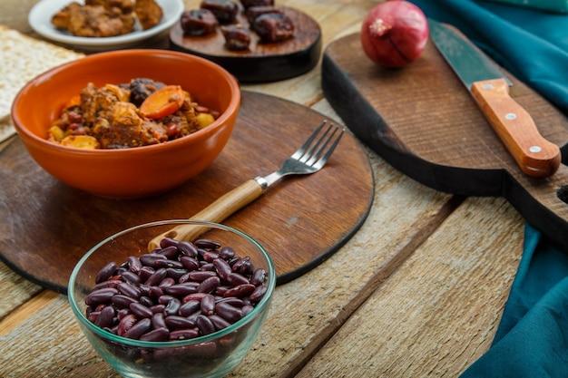 Plat juif chelnt avec de la viande dans une assiette sur une table en bois sur un support à côté des ingrédients. photo horizontale