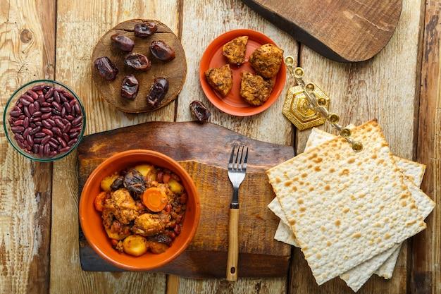 Plat juif chelnt avec de la viande sur un support à côté du pain azyme, de la fourchette et des ingrédients. photo horizontale