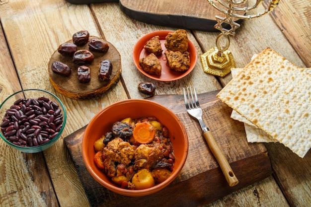 Plat juif chelnt avec de la viande sur un support à côté du pain azyme, de la fourchette et des ingrédients.