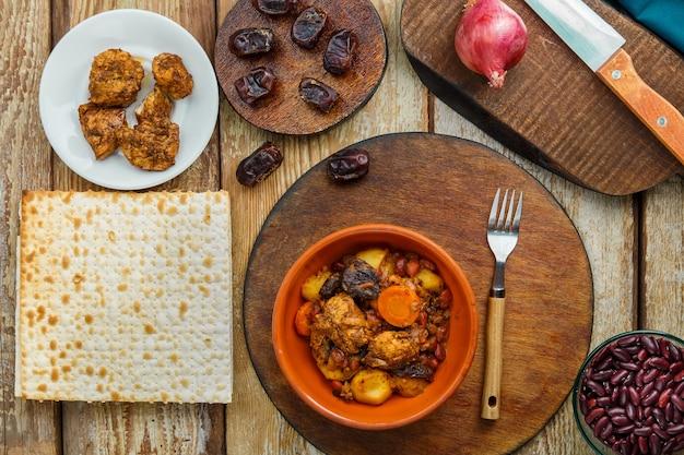 Plat juif chelnt avec de la viande sur la table dans une assiette près des ingrédients et du pain azyme. photo horizontale
