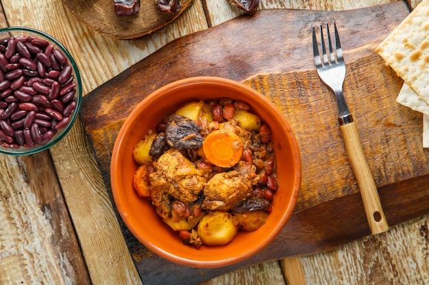 Plat juif chelnt avec de la viande sur la table dans une assiette sur un support à côté des ingrédients et du pain azyme.