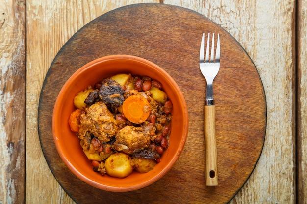 Plat juif chelnt avec de la viande sur la table dans une assiette sur un support rond. photo horizontale