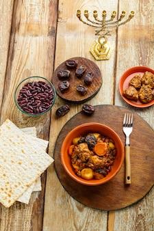 Plat juif cholent avec ingrédients de viande et menorah sur la table