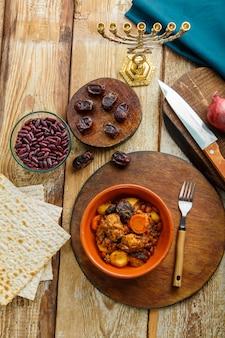 Plat juif cholent avec des ingrédients de viande et de la menorah sur la table.