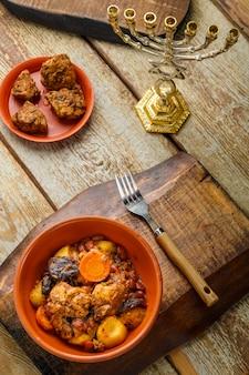 Plat juif fermé avec de la viande sur une table en bois près du pain azyme et des ingrédients. photo verticale