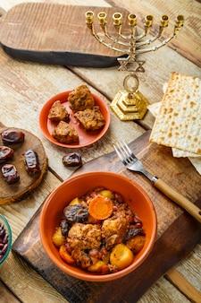 Plat juif fermé avec de la viande sur une table en bois près du pain azyme et des ingrédients.