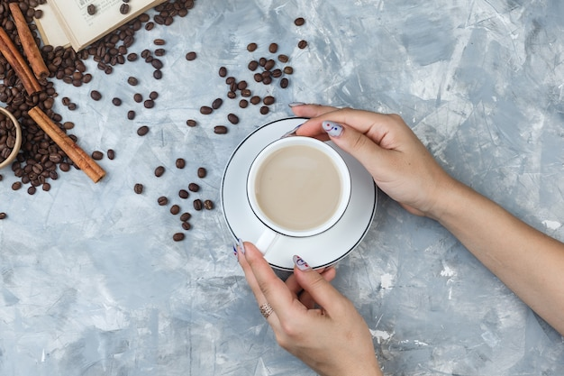 Plat laïc des mains féminines tenant une tasse de café avec des grains de café, des bâtons de cannelle, livre sur fond de plâtre gris. horizontal