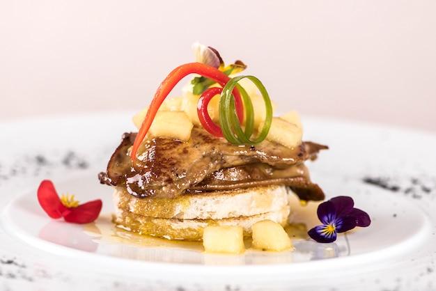 Plat luxueux avec morceaux de foie de canard, d'ananas et de mangue, sauce sucrée