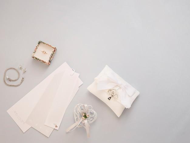 Plat minimal poser avec accessoires de mariage sur fond clair.