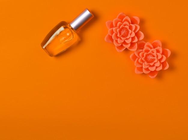 Plat minimalisme d'une bouteille de parfum et de bougies en forme de fleurs sur orange.