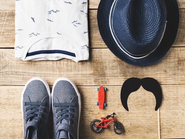Plat de mode hipster pour enfants avec des vêtements et des accessoires sur bois