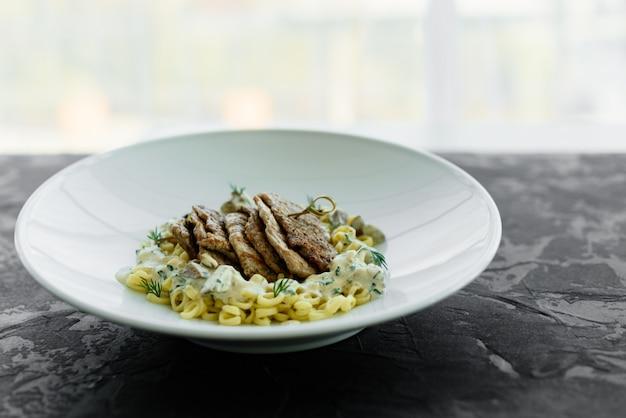 Plat avec des morceaux de viande, pâtes, légumes verts, sauce d'un foie gras et de la terre d'olive