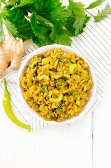 Plat national indien kichari à base de haricot mungo, riz, tige de céleri, épinards, piment fort et épices dans un bol sur une serviette, gingembre sur fond de planche de bois clair d'en haut