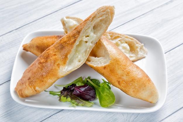 Plat national khakuri, plat national abkhaze ou géorgien, avec fromage et salade sur une assiette et une table en bois blanche