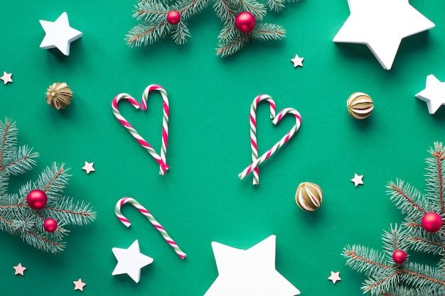 Plat de noël créatif avec des brindilles de sapin, des cannes de bonbon disposées en coeurs, des boules de verre rouges et des fruits de citron vert secs. coffrets cadeaux en papier en forme d'étoiles. fond de noël zéro déchet, matériaux naturels.