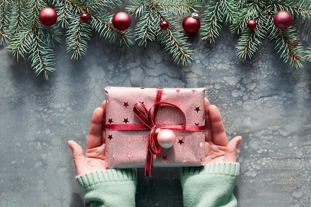 Plat de noël créatif posé sur un tableau d'art fluide acrylique gris. mains féminines en pull vert menthe tenant une boîte cadeau enveloppée dans du papier rose avec un ruban rouge. brindilles de feu et de houx avec des boules de couleur bordeaux.