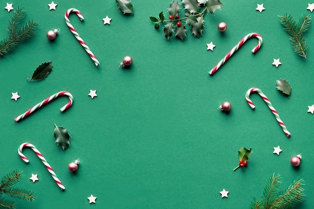 Plat de noël géométrique branché avec des cannes de bonbon, des brindilles de houx et de sapin, des étoiles en bois et des bibelots en verre avec espace de texte