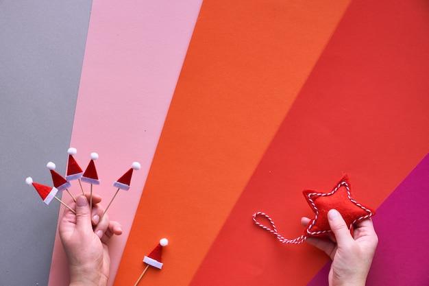 Plat de noël avec des mains féminines tenant une étoile textile et de petits chapeaux de santa. vue de dessus du fond de papier en couches géométriques multicolores en couches rouge, orange, rose, magenta et argenté d'en haut.