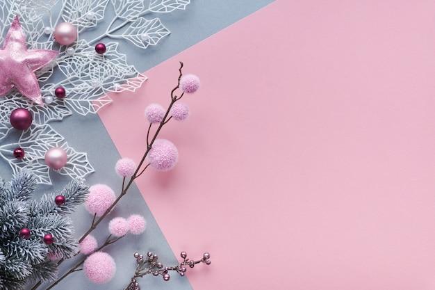 Plat de noël posé sur fond de papier bicolore, rose et argent, et copie-espace. brindilles décoratives d'hiver blanches avec des feuilles géométriques brillantes et des boules en textile doux et des boules de noël en verre dispersées.