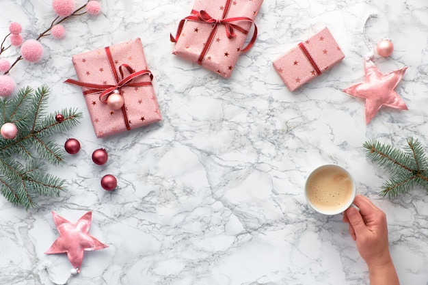 Plat de noël posé sur une table en marbre avec copie-espace. main tenant la tasse de café. décorations d'hiver: brindilles de sapin, étoiles douces et babioles roses