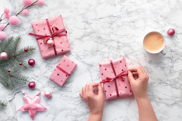 Plat de noël posé sur une table en marbre. les mains nouent le ruban sur un cadeau de noël enveloppé. tasse à café et décorations d'hiver: brindilles de sapin, bibelots roses et étoiles.