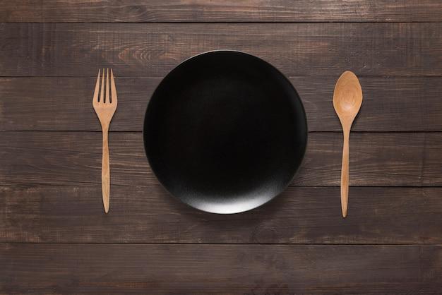 Plat noir, fourchette et cuillère sur le fond en bois. vue de dessus