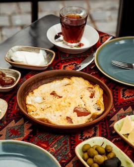 Plat d'oeufs et saucisses dans un moule en poterie servi pour le petit déjeuner