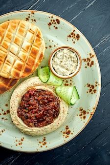 Un plat oriental classique - houmous de pois chiches avec légumes cuits au four et huile d'olive servi avec pita au four dans une assiette de table en bois