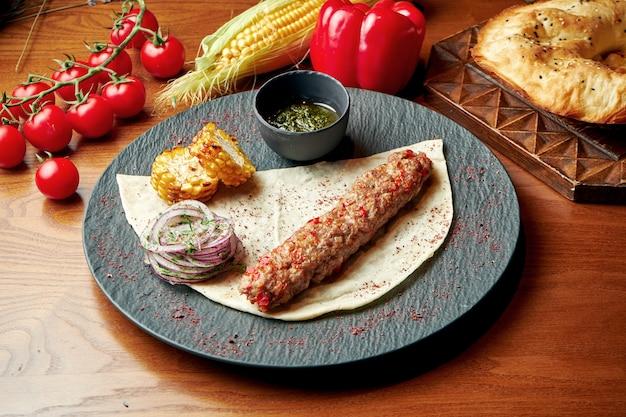 Un plat oriental de kebab d'agneau à base de viande hachée avec lavash et sauce verte. nourriture halal