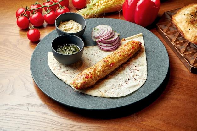 Un plat oriental de kebab de poulet à base de viande hachée avec lavash et sauce verte. nourriture halal