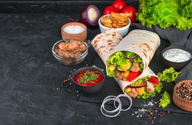 Plat oriental traditionnel-shawarma avec poulet et frites sur un mur noir. fast food. vue latérale, horizontale.