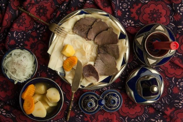 Plat oriental de viande bouillie et de pâte sur une nappe