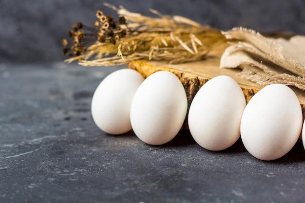 Plat de pâques la composition rustique des œufs blancs frais en ovule sur fond sombre. zéro déchet, matériau écologique et naturel. concept d'agriculture et de saine alimentation. fermer