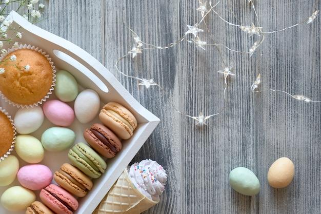 Plat de pâques avec macarons, muffins et œufs en massepain jn un plateau décoratif sur bois gris texturé