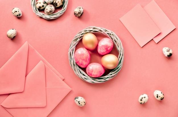 Plat de pâques posé sur papier rose avec des œufs de caille, des cartes de voeux et des enveloppes.