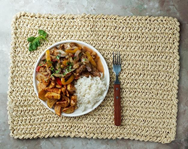 Plat péruvien lomo saltado, fait de filet de boeuf avec oignon rouge, piment jaune, tomates, avec frites de pomme de terre et riz.