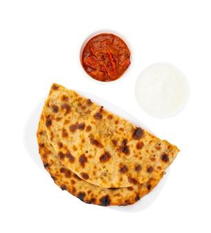 Plat de petit déjeuner indien aloo paratha servi avec curd et cornichons
