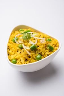 Plat de petit-déjeuner indien poha également connu sous le nom de pohe ou aalu poha composé de riz battu ou de riz aplati. les flocons de riz sont légèrement frits dans de l'huile avec des épices servis avec du thé chaud