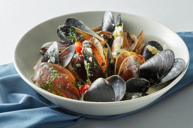 Plat de photos de moules à la sauce tomate, ouvert, prêt à manger sur un fond clair