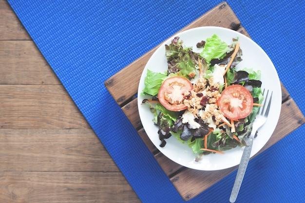 Plat plat de plat à salade sur tapis de yoga, alimentation saine