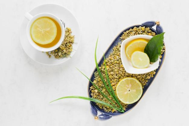 Plat à plat de thé au citron et bol de feuilles